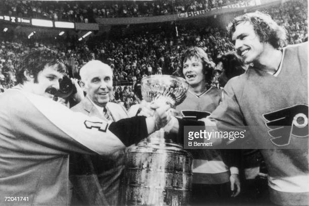 Canadian hockey players Bernie Parent and Bill Clement of the Philadelphia Flyers clasp hands as National Hockey League President Clarence Campbell...