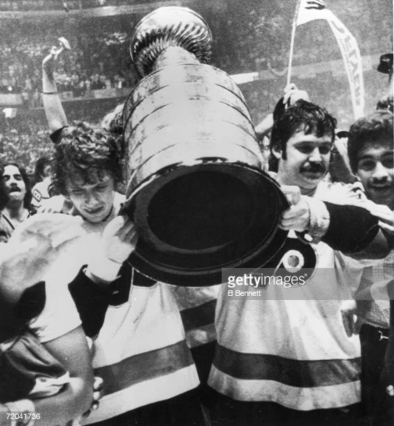 Canadian hockey players Bobby Clarke and Bernie Parent of the Philadelphia Flyers carry the Stanley Cup as they celebrate their serieswinning victory...