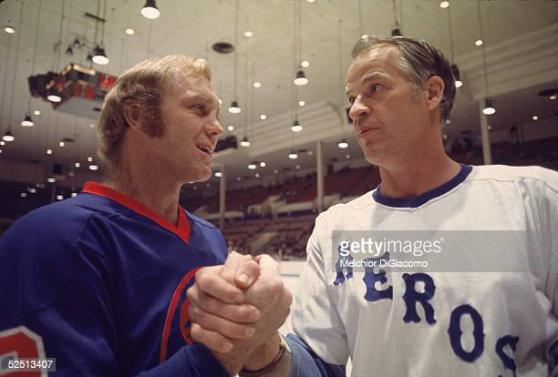 Canadian hockey players Bobby Hull of the Winnipeg Jets and Gordie Howe of the Houston Aeros clasp hands on the ice before a game 1970s