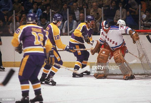Canadian hockey players Marcel Dionne Dave Taylor and Charlie Simmer of the Los Angeles Kings hover around the net during a game against the New York...