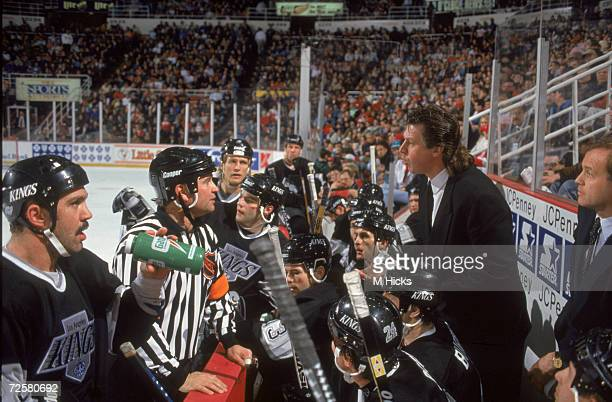 Canadian ice hockey coach Barry Melrose of the Los Angeles Kings shares words with an official during a game while his team listens in February 1995