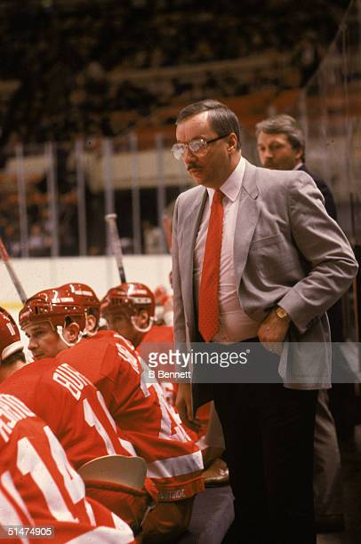 Canadian ice hockey coach Jacques Demers stands behind the bench and watches the action as his team the Detroit Red Wings play at home Detroit...