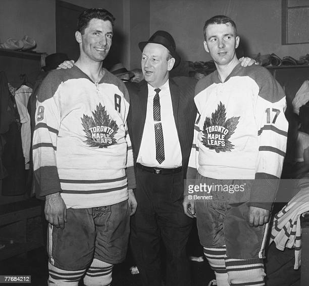 Canadian ice hockey coach Punch Imlach of the Toronto Maple Leafs poses with two of his players Andy Bathgate and Don McKenney in the locker room...