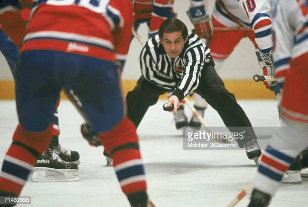 Canadian ice hockey linesman Ray Scapinello prepares to drop the puck during a face-off between the Montreal Canadiens and the New York Rangers at...