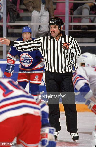 Canadian ice hockey linesman Rod Asselstine makes a call in a game between the Winnipeg Jets and the New York Rangers New York New York early 1990s