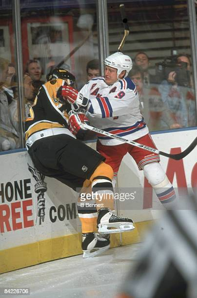 Canadian ice hockey player Adam Graves of the New York Rangers checks Swedish player Peter Popovic of the Boston Bruins into the baords during a game...