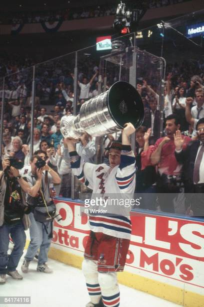 Canadian ice hockey player Adam Graves of the New York Rangers lifts the Stanley Cup above his head in celebration on the ice after the team's...