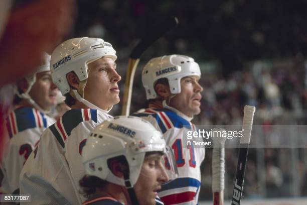 Canadian ice hockey player Adam Graves of the New York Rangers watches the onice action from the bench November 1995 Among his visible teammates is...