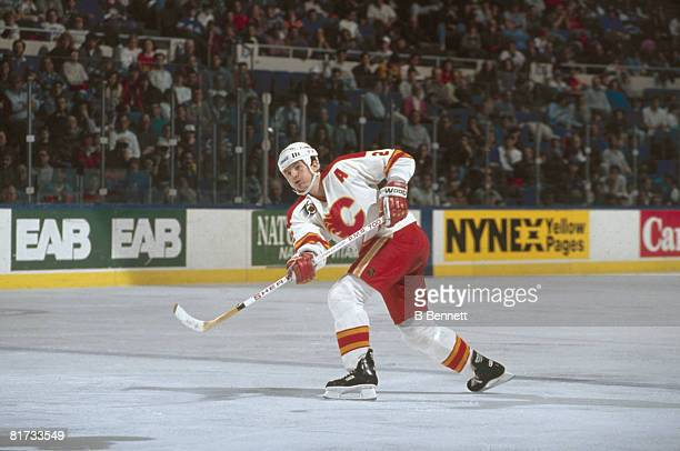 Canadian ice hockey player Al MacInnis of the Calgary Flames fires the puck along the ice during a game early 1980s to early 1990s