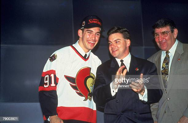 Canadian ice hockey player Alexandre Daigle wearing an Ottawa Senators jersey and cap over his suit waves from the stage at the NHL Entry Draft in le...