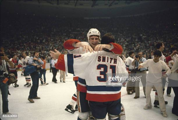 Canadian ice hockey player Billy Smith, goalkeeper for the New York Islanders, embraces teammate Duane Sutter as their team defeated the Philadelphia...