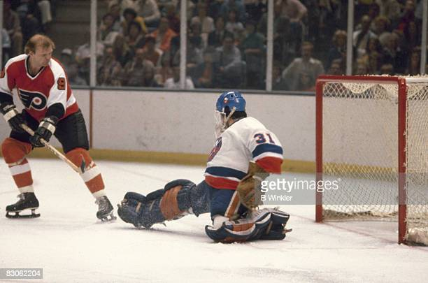 Canadian ice hockey player Bob Kelly of the Philadephia Flyers tries a shot on goal as Billy Smith goalkeeper of the New York Islanders reaches out...