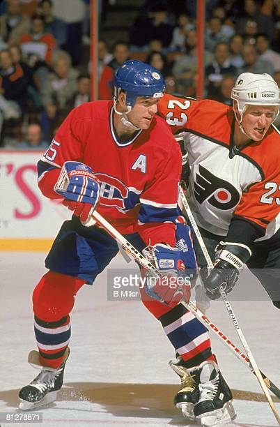 Canadian ice hockey player Bobby Smith of the Montreal Canadiens jostles with Finnish player Ilkka Sinisalo of the Philadelphia Flyers during a game...