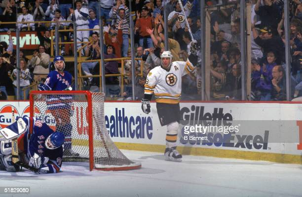 Canadian ice hockey player Cam Neely of the Boston Bruins raises his stick in victory after scoring a goal during a game against the New York Rangers...