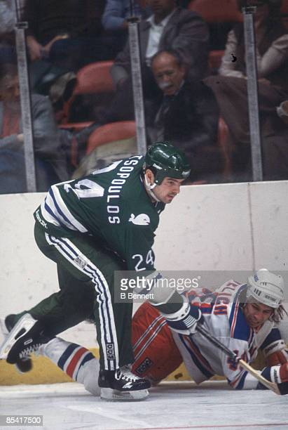 Canadian ice hockey player Chris Kotsopoulos of the Hartford Whalers tangles with American player Mark Pavelich of the New York Rangers during a game...