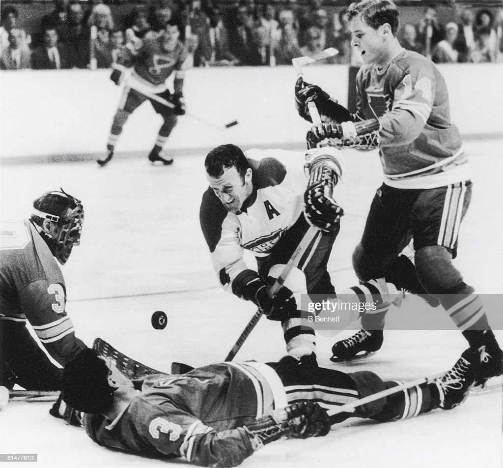 Canadian ice hockey player Claude Provost (center, in white) tooks for the puck amid downed St. Louis Blues players Al Arbour (#3, forground) and goalie Jacques Plante (left) while the Blues' Tim Ecclestone approaches at right, during game three of the Stanley Cups finals, St. Louis, Missouri, May 1, 1969. The Canadiens went on the win both the game and the series.