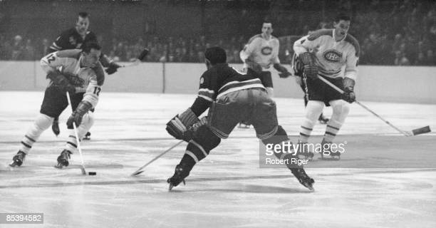 Canadian ice hockey player Dickie Moore advances the puck towards the New York Rangers' goalkeeper while Moore's teammate Jean Beliveau provides...