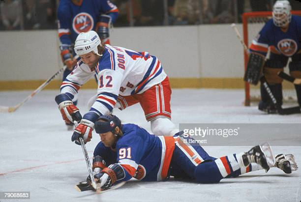 Canadian ice hockey player Don Maloney of the New York Rangers battles with a prostrate Butch Goring of the New York Islanders during a game New York...