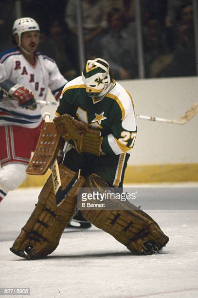 Canadian ice hockey player Gilles Meloche goalkeeper for the Minnesota North Stars catches the puck in his glove during a game against the New York...