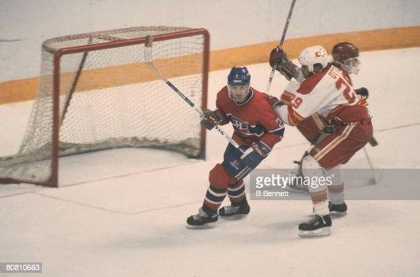 Canadian ice hockey player Guy Carbonneau of the Montreal Canadiens and American Joel Otto of the Calgary Flames skate in front of the Flames' net...