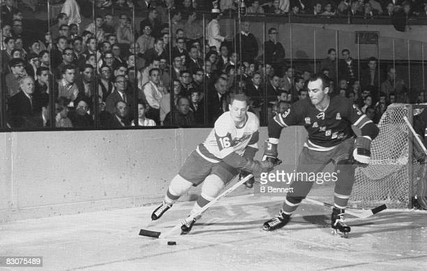 Canadian ice hockey player Harry Howell of the New York Rangers moves the puck away from Bruce MacGregor of the Detroit Red Wings who holds onto...