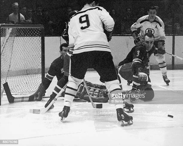 Canadian ice hockey player Harry Howell of the New York Rangers defends against Johnny Bucyk and Phil Esposito of the Boston Bruins during a game...
