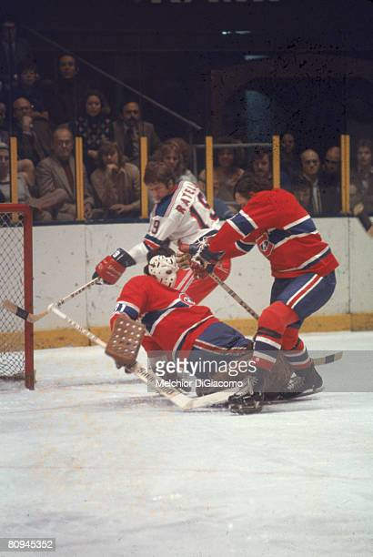 Canadian ice hockey player Michel Larocque goalkeeper for the Montreal Canadiens goes to the ice to make a save while Jean Ratelle of the New York...