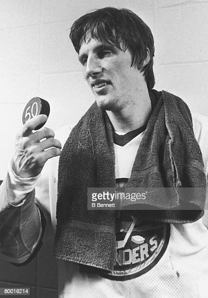 Canadian ice hockey player Mike Bossy of the New York Islanders holds up the puck with which he scored his 50th goal in 50 consecutive games Nassau...