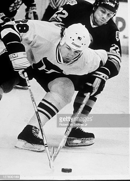 Canadian ice hockey player Paul Lawless of the Hartford Whalers battles for the puck with a player from the Boston Bruins during a game, Hartford,...