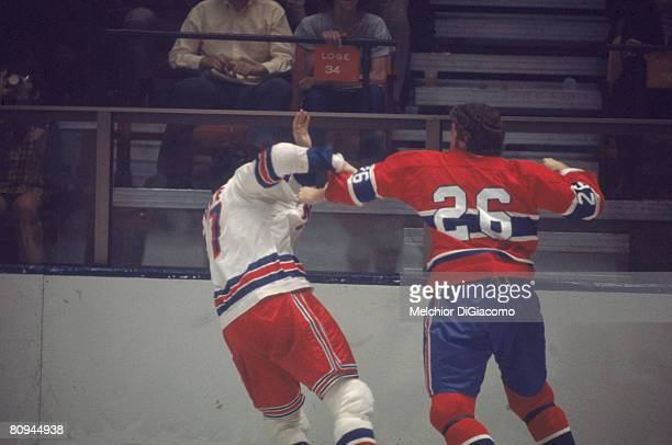 Canadian ice hockey player Pierre Bouchard of the Montreal Canadiens takes a swing at Ted Irvine of the New York Rangers during a game early 1970s