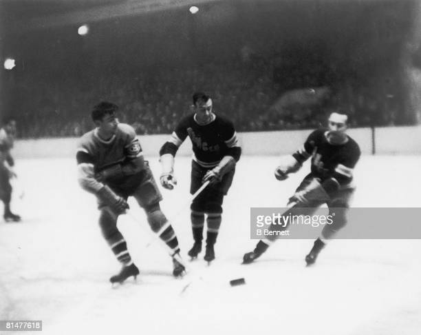 Canadian ice hockey player Sylvio Mantha of the Montreal Canadians flicks a pass across two undentified New York Rangers players during a game...