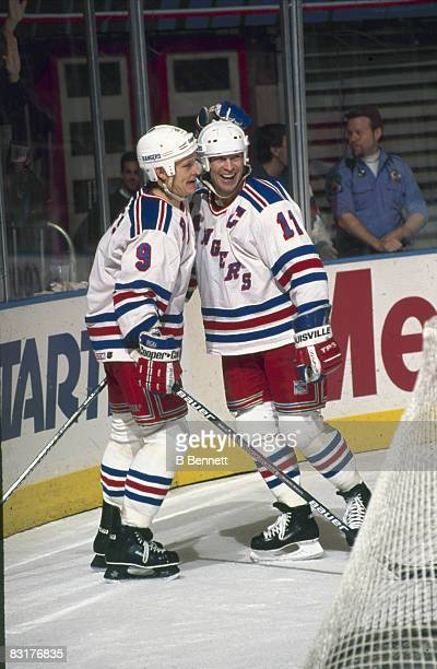 Canadian ice hockey players Adam Graves and Mark Messier of the New York Rangers smile as they celebrate behind the net during a game 1990s