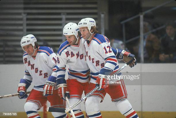 Canadian ice hockey players Ed Johnstone and brothers Dave and Don Maloney of the New York Rangers on the ice during a game October 1982