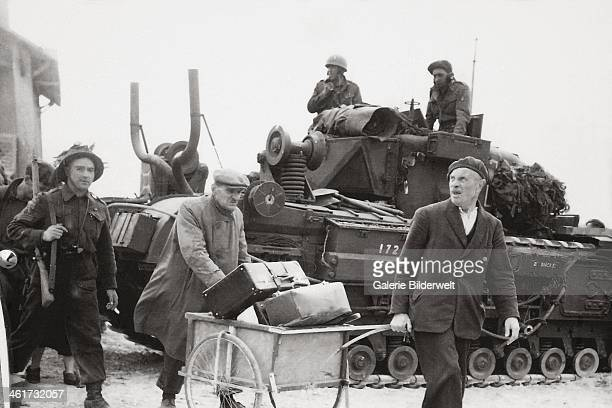 Canadian infantry soldiers and civilians after the landing at Juno Beach. June 1944. Bernières-sur-Mer, Normandy, France.