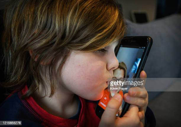 Canadian Jetsun Frayer 6 years old and son of the photographer kisses the phone as he talks with his mother journalist Janis Mackey Frayer from a...