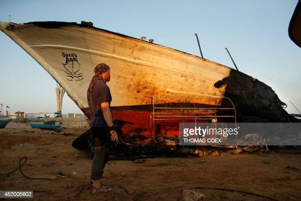 Canadian John Godfrey a chief member of the peace activist boat 'Gaza's Ark' checks the damage to his burnt boat following an Israeli air strike...