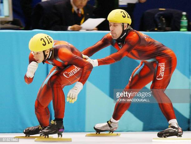 Canadian Jonathan Guilmette is pushed by teammate Marc Gagnon during the men's 5000m relay final of the short track speed skating at the Olympic Ice...