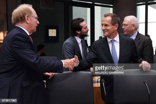 Canadian lawyer Richard McLaren shakes hands with the president of the German Olympic Sports Confederation Alfons Hoermann next to the Director of...