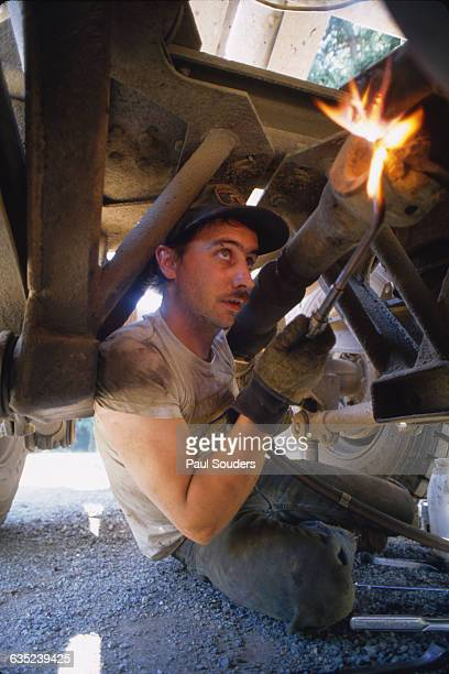 Canadian log truck driver Lyle Ayers uses a torch for unyeilding bolts on the drive shaft of his truck during a Saturday afternoon maintenance in...