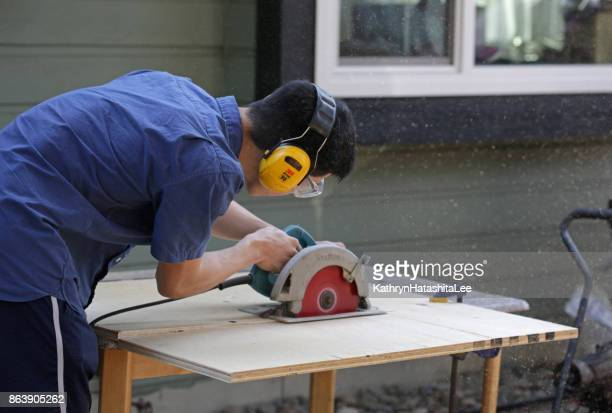 canadian man cuts plywood with circular saw outdoors - circular saw stock photos and pictures