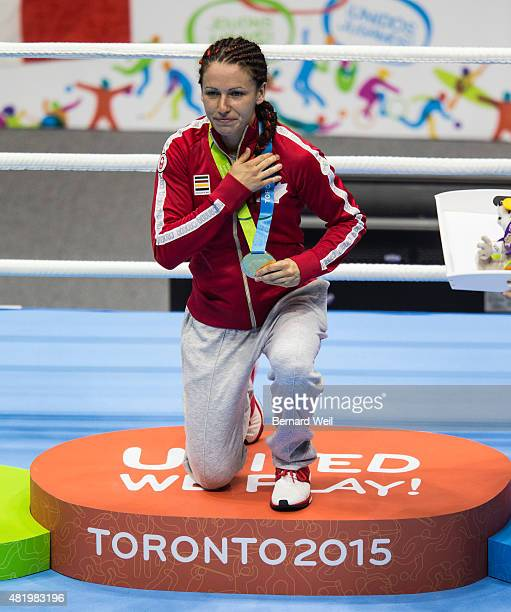OSHAWA ON JULY 25 Canadian Mandy Bujold does a sign of the cross during the medal ceremony after the split decision went in her favor after defeating...