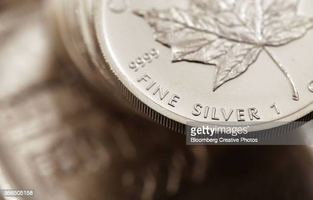 canadian maple leaf one ounce silver coins sit on a one kilogram silver bar - silver metal stock pictures, royalty-free photos & images