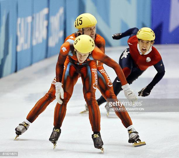 Canadian Marc Gagnon pushes teammate Jonathan Guilmette US Apolo Anton Ohno tries to overtake them during the men's 5000m relay final of the short...