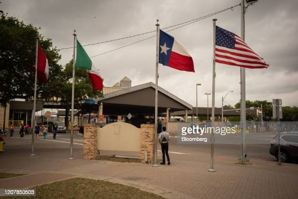 Canadian, Mexican, Texas, and American flags fly at a border crossing in Brownsville, Texas, U.S., on Friday, March 20, 2020. PresidentDonald...