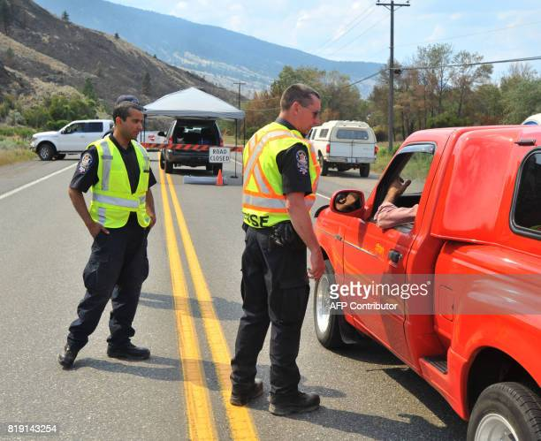 Canadian Mounted Police and Commercial Vehicle Safety and Enforcement block traffic from going on highway 97 north of Cache Creek BC July 19 2017 as...