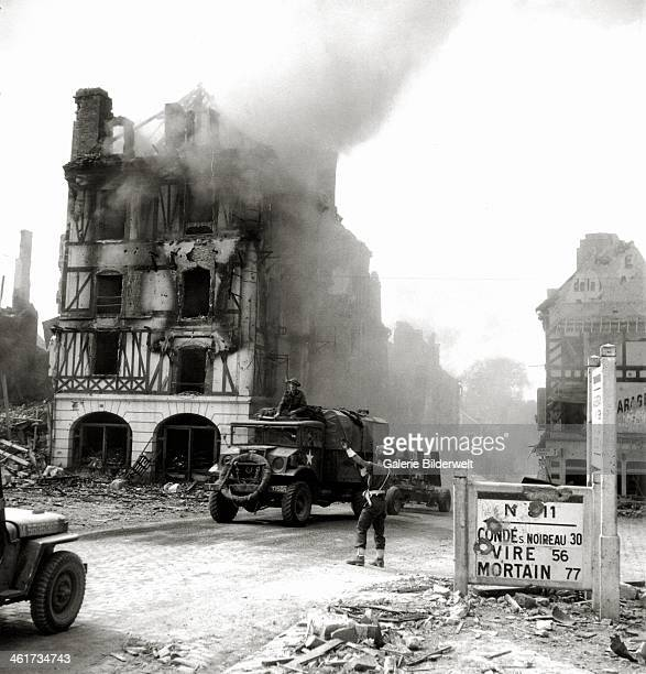 Canadian MP , controls the traffic on place Saint Gervais. 17th August 1944. Buildings are in ruins and on fire. A Chevrolet truck towing a Bofors...
