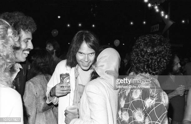 Canadian musician Neil Young chats with singer Nicolette Larson at the premiere party for his concert movie 'Rust Never Sleeps' held on the lot of...