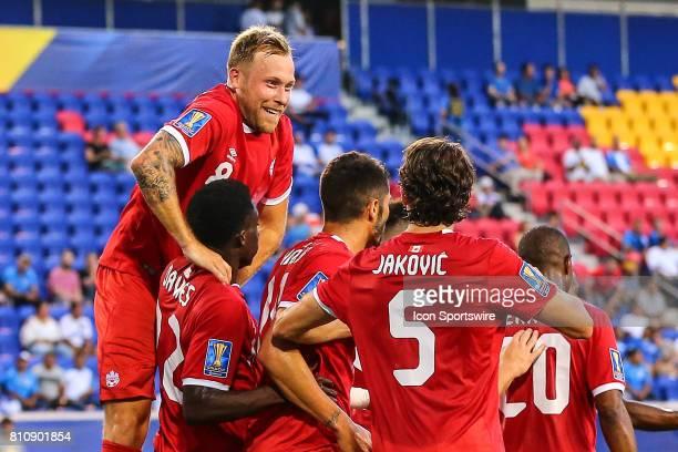Canadian National Soccer Team midfielder Scott Arfield jumps on teammate Canadian National Soccer Team midfielder Alphonso Davies after a goal by...