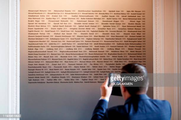 Canadian official takes a photograph of the names of the victims of the Ukrainian plane shot down in Iran before a meeting of the International...
