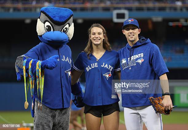 Canadian Olympian in Rio Penny Oleksiak poses with mascot Ace and Aaron Sanchez after throwing out the first pitch before the start of the Toronto...